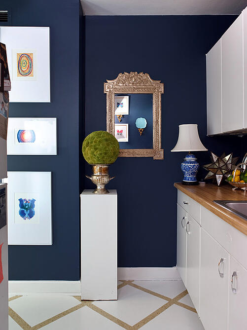 Navy blue walls with white kitchen cabinets